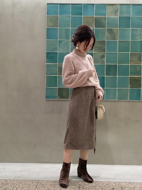 ピンクのニットにグレーのスエードスカートを合わせた女性