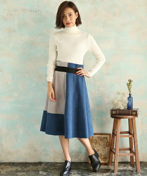 白ニットにブルーのスエードスカートを合わせた女性