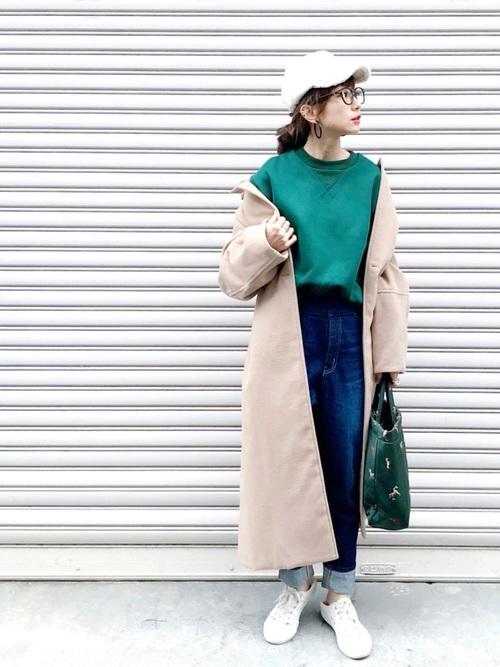 グリーンのトップスにデニムを合わせてベージュのコートを羽織った女性
