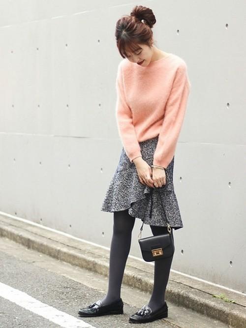 ピンクニットにグレーのスカートを合わせて黒いバッグを持った女性