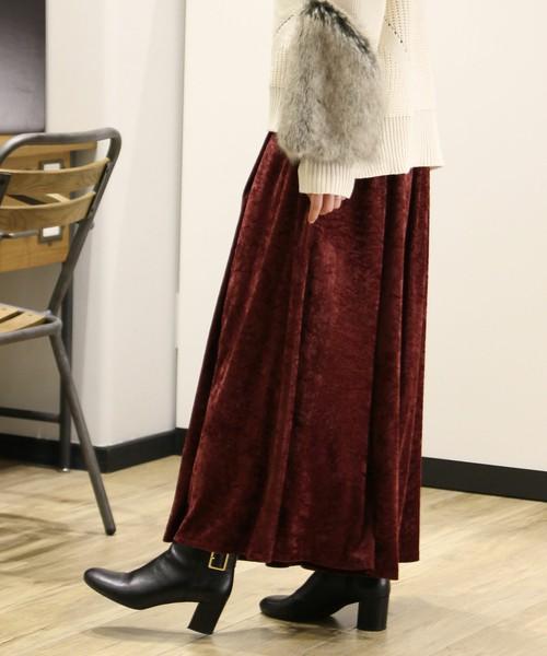 ボルドーのベロアパンツを履いた女性