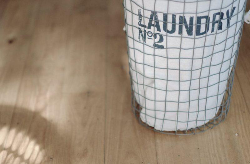フローリング床の上に置かれたシルバーのアルミ製洗濯かご