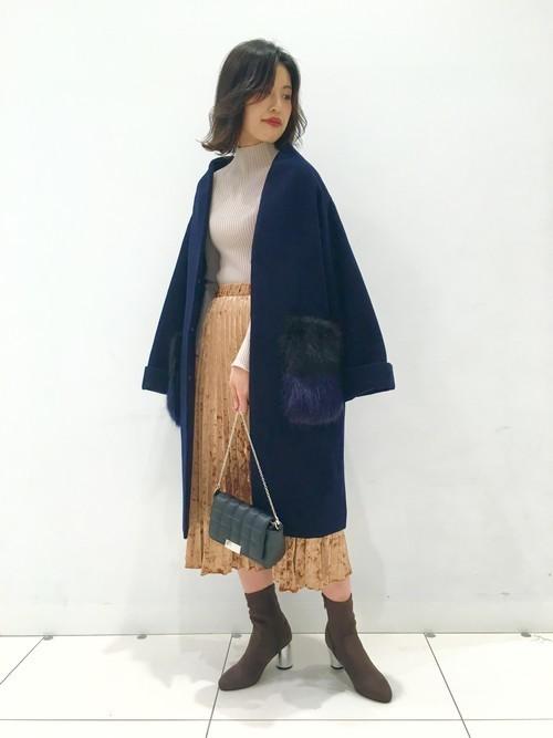 ハイネックニットにブラウンのベロアプリーツスカート、ネイビーのファーポケットコートを合わせたコーデ
