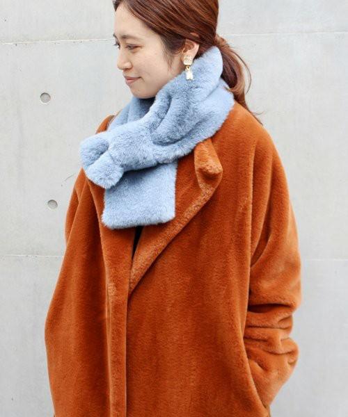 オレンジのエコファーコートに水色マフラーをした女性