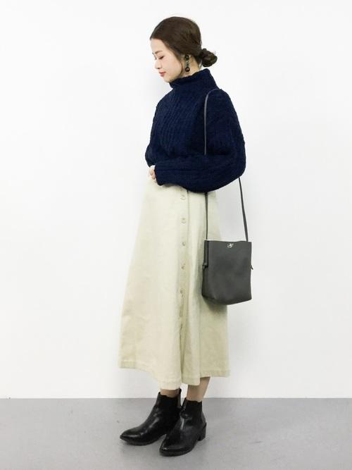 ネイビーのタートルニットに白のコーデュロイスカートを履いた女性