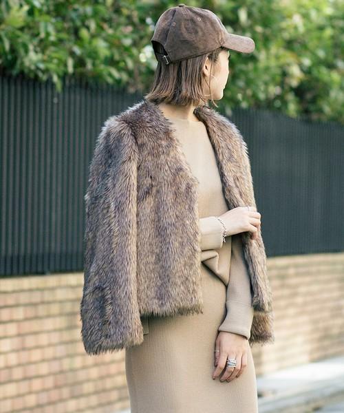 ベージュワンピにブラウンのファーコートを着た女性