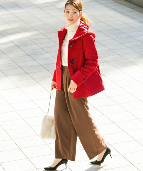 白ハイネックニットにワイドパンツを合わせて赤いコートを羽織った女性