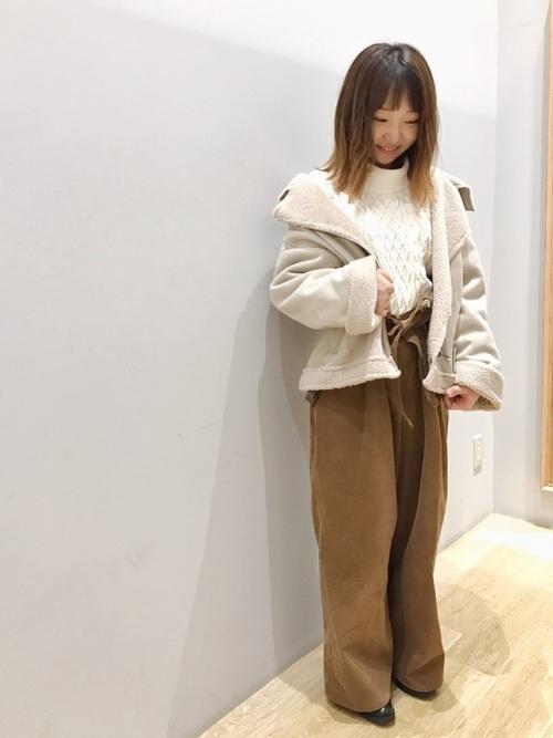 白ニットにキャメルのパンツを合わせて、ショート丈のムートンコートを羽織った女性