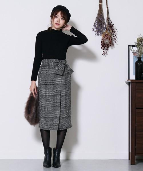 黒ニットにグレンチェックのハイウエストタイトスカートを合わせて、ファーバッグを持った女性