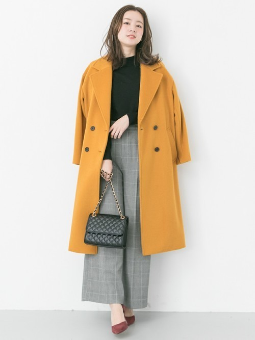 チェックワイドパンツにイエローチェスターコートを着た女性