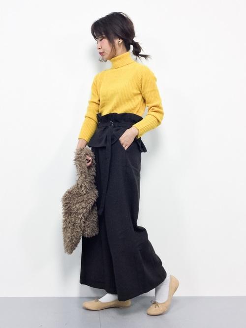 黄色のタートルネックニットにブラウンのワイドパンツ、バレエシューズを履きボアバッグを合わせたコーデ