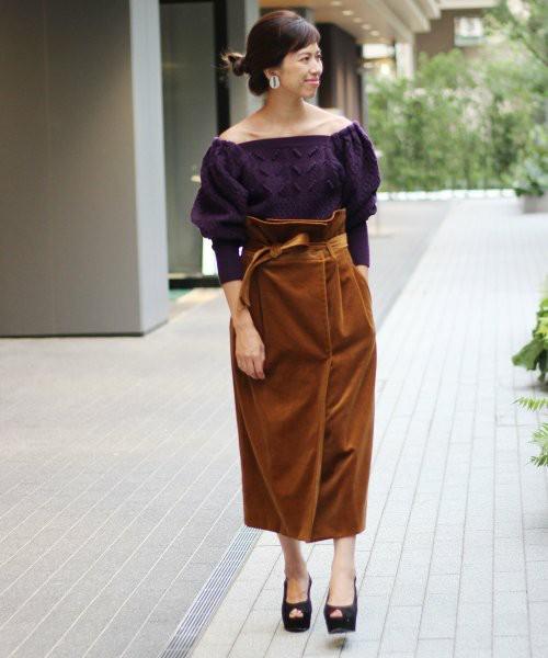 紫ニットにブラウンのベロアスカートを履いた女性