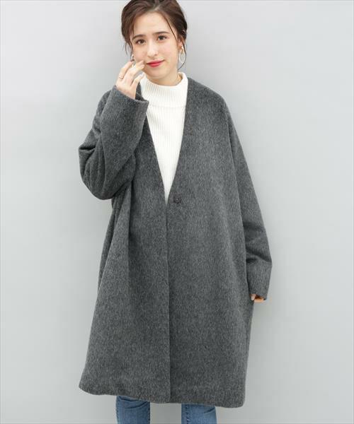 白ニットにグレーのノーカラーコートを着た女性