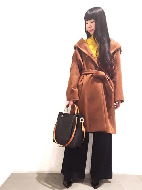 黄色のトップス、デニムワイドパンツにキャメルのガウンコートを着た女性