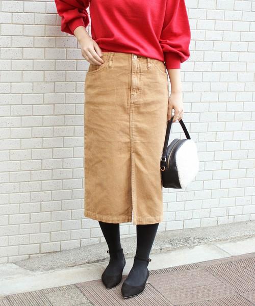 赤ニットにコーデュロイタイトスカートを履いた女性