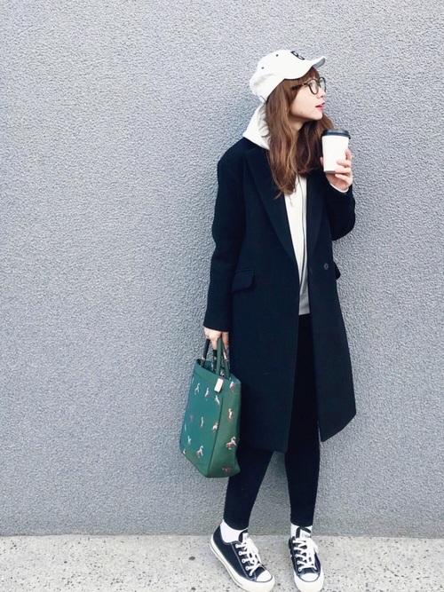 白いパーカーに黒いパンツを合わせてチェスターコートを着た女性