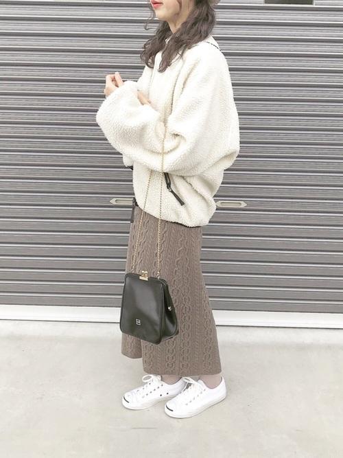 ボアブルゾンにニットのスカートを合わせて白いスニーカーを履いた女性