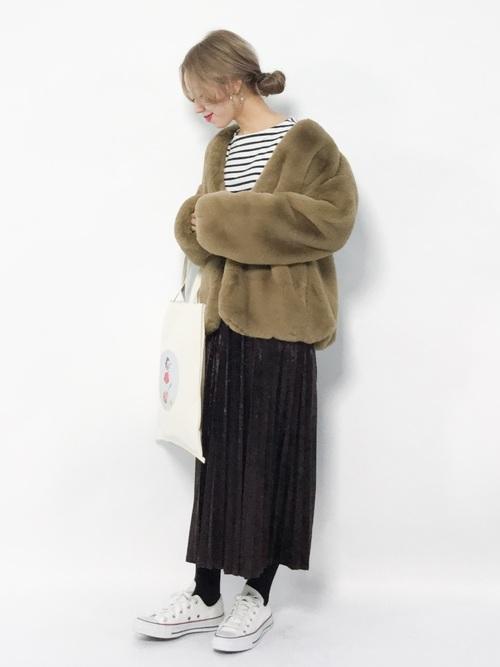ボーダートップスにプリーツスカートを合わせてファーバッグを持った女性