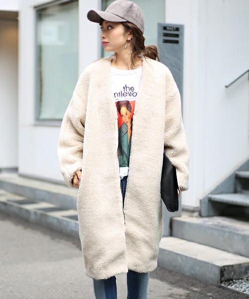 キャップをかぶり白ボアコートを着た女性
