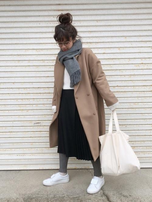 白いトップスに黒いスカートを合わせてキャメルのコートを着た女性