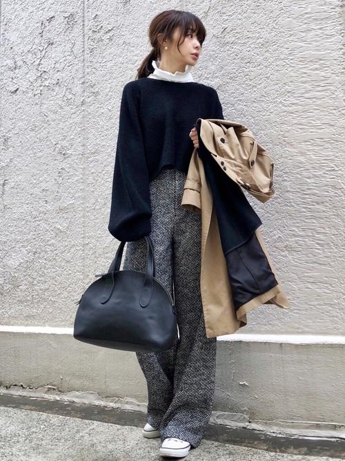 黒のニットにフリルブラウスを合わせてグレーのワイドパンツを履いた女性