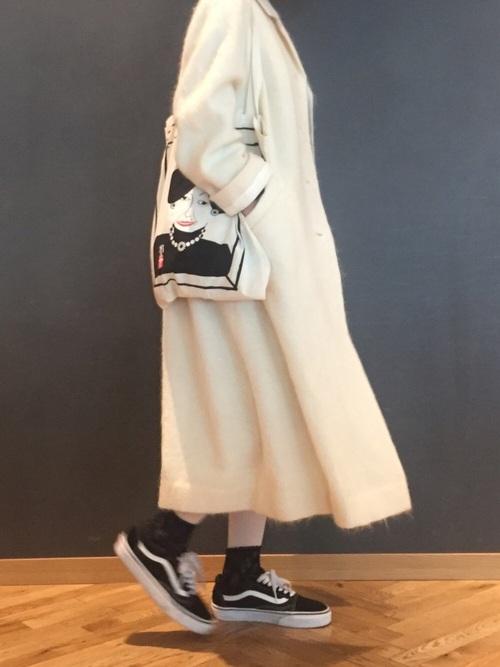 白タイツの上に黒靴下を重ね履きした白いコートを着た女性