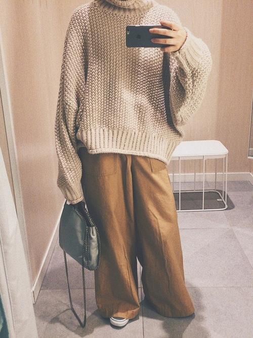 ベージュのニットにベージュのワイドパンツを履いた女性