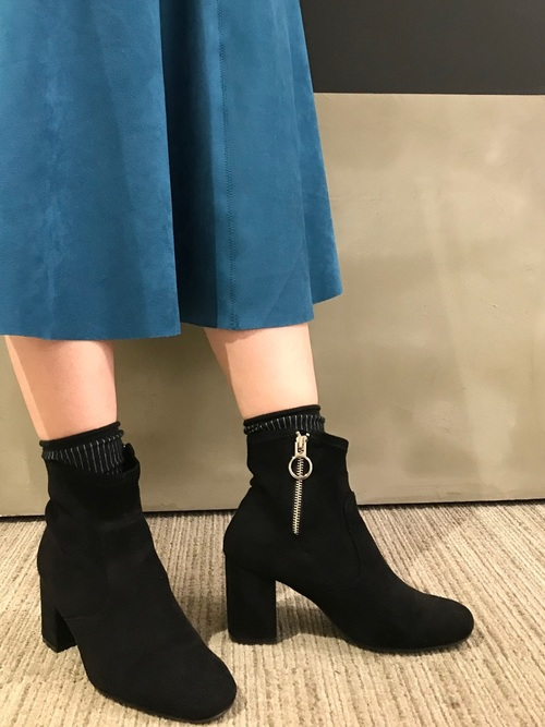 青のスカートに黒のベロアブーツを合わせる女性