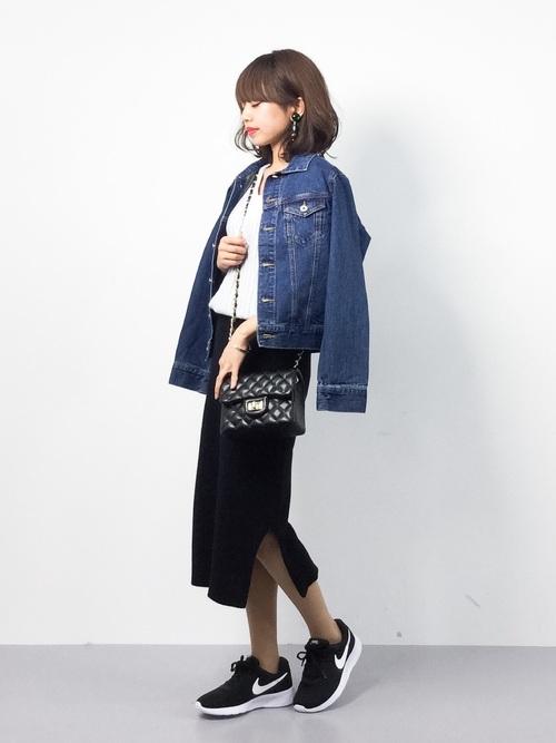 グレーのリブニット、黒のタイトスカートにデニムジャケットを着た女性