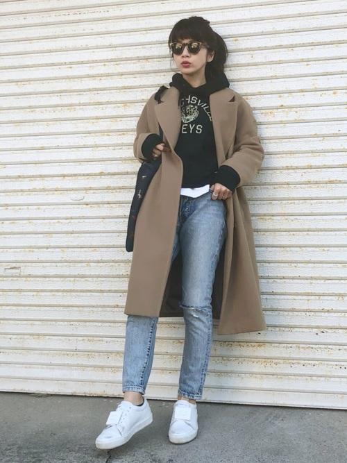 黒のパーカーにデニムパンツ、キャメルのチェスターコートを羽織り、サングラスをかけた女性