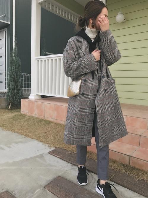 白のタートルネックニットに黒のパーカー、チェックのチェスターコートを羽織り、スニーカーを合わせたコーデ