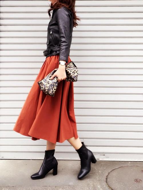 黒のライダースジャケットに赤のフレアスカートを履いた女性