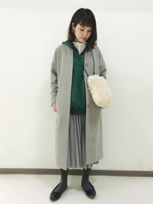 グリーンのパーカーにシフォンスカートを履いてグレーのコートを羽織った女性