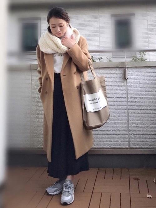 白のTシャツ、ネイビーのスカートにキャメルのチェスターコートを着た女性