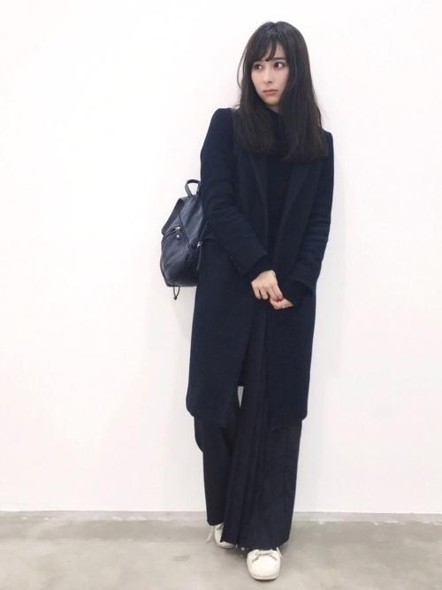黒のトップス、ネイビーのワイドパンツにネイビーのコートを着た女性