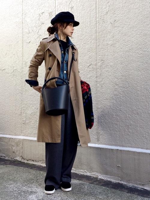 デニムジャケットにトレンチコート、デニムパンツに、バケツバッグをかけた女性