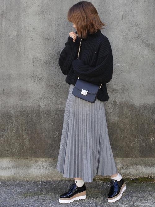 黒のタートルネックにグレーのプリーツスカートを合わせる女性