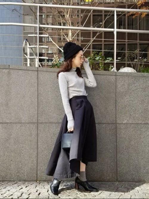 グレーのタートルネックニットに黒のスカートを合わせる女性