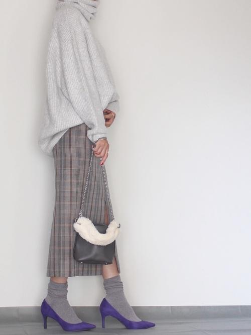 グレーのニットとチェックのスカートを合わせたワントーンコーデにパープルのパンプスを合わせた女性