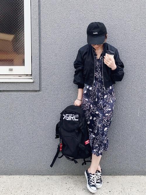 ネイビーの花柄ワンピースに黒のブルゾンを羽織って、黒のキャップをかぶり大きめのバッグパックを持った女性