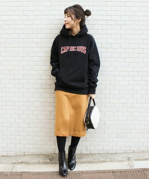 黒パーカーにイエロースカートを履いた女性