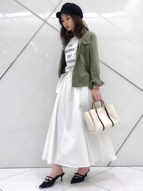 白のロゴTシャツに白のチノスカートを合わせて、カーキのミリタリーシャツを羽織った女性