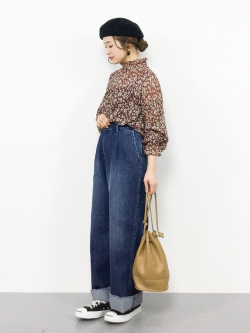 ブラウンの花柄ブラウスにデニムワイドパンツを履いた女性