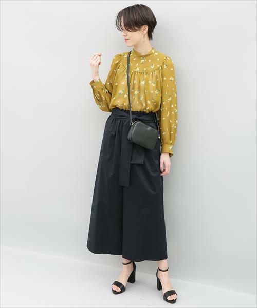 黄色の花柄ブラウスに黒のガウチョパンツを履いた女性