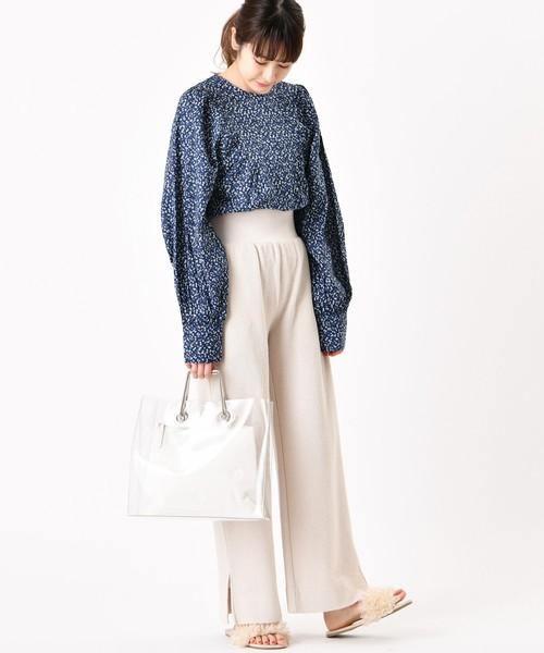 ネイビーの花柄ブラウスに白のワイドパンツを履いた女性