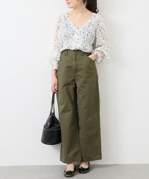 白の花柄ブラウスにカーキのワイドパンツを履いた女性