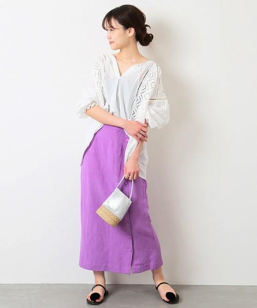 白のレースブラウスにムラサキのタイトスカートを履いた女性