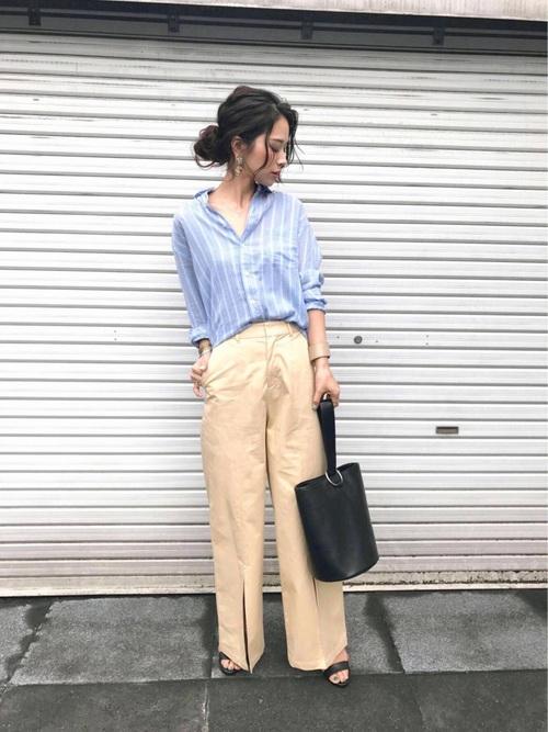 ブルーのストライプシャツにベージュのワイドパンツを履いた女性