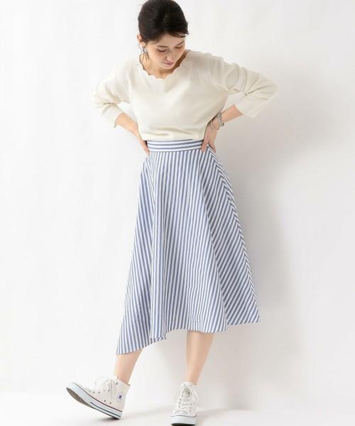 白のスカラップトップスにブルーのストライプスカートを履いた女性