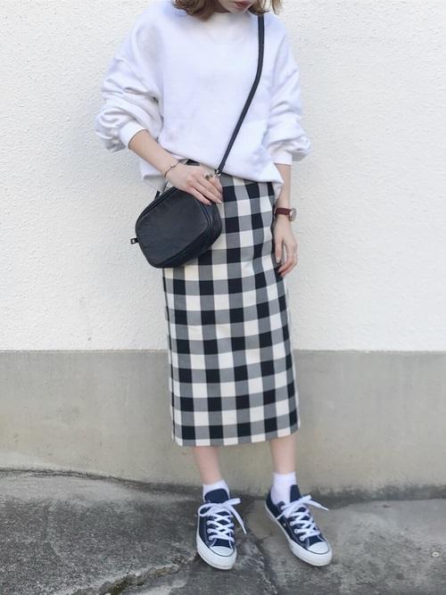 白のスウェットにギンガムチェックのタイトスカートを履いた女性